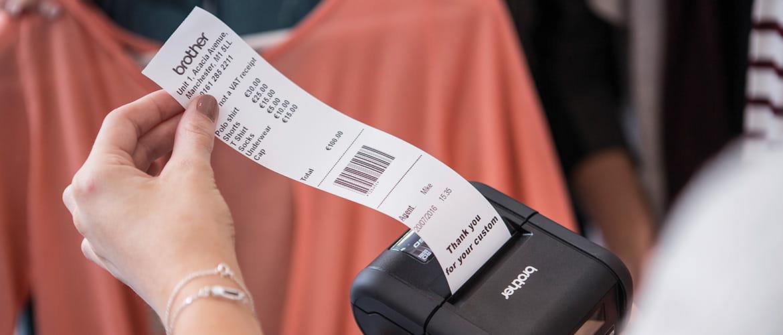 Frau in Bekleidungsgeschäft zieht Kassenbeleg aus Etikettendrucker