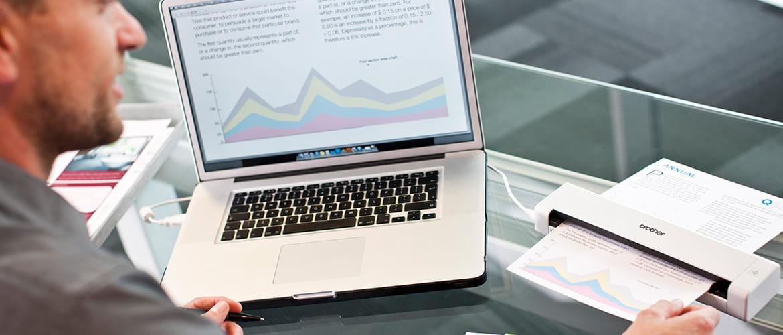 Mann scannt farbiges Dokument mit Diagrammen über mobilen Scanner ein und betrachtet es am Laptop.