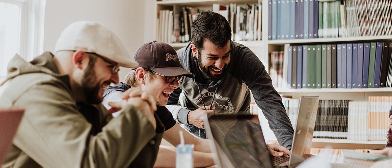Drei lachende Männer schauen auf einen Laptop Bildschirm.