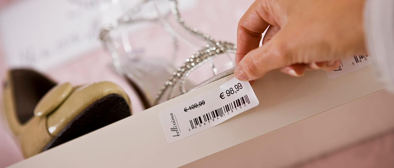 Reduziertes Preis-Etikett wird an Damenschuh-Regal angebracht.