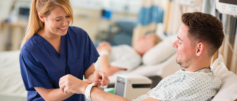 Krankenpflegerin legt Patient Patientenarmband aus Etikettendrucker um Handgelenk