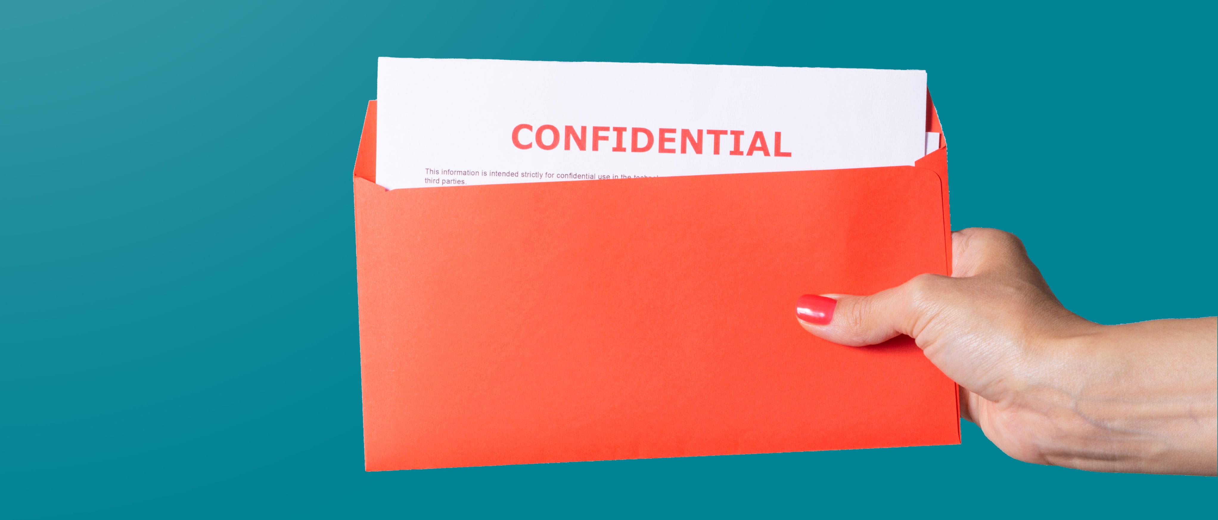 Hand hält einen roten Briefumschlag aus dem ein weißer Brief mit roter Aufschrift Confidential herausragt.