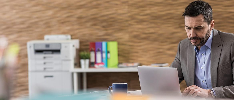 Mann am Schreibtisch tippt in seinen Laptop. Im Hintergrund steht ein Tintenstrahldrucker.