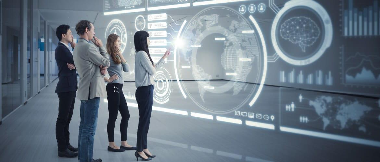 Vier Menschen stehen in Büro vor einem Hologramm
