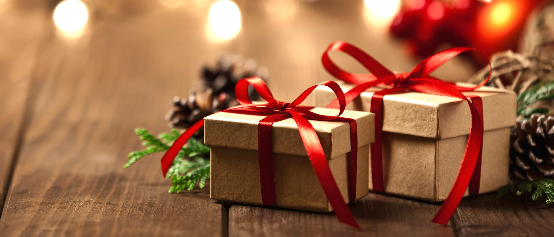 Geschenkboxen mit rotem Geschenkband auf Holztisch