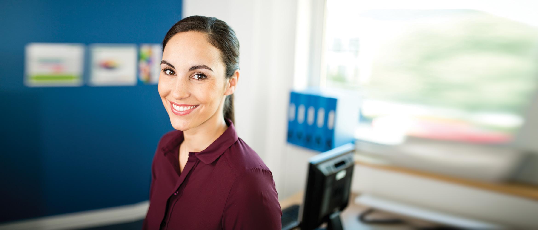 Dunkelhaarige Frau lächelt in Kamera, Büroumgebung im Hintergrund