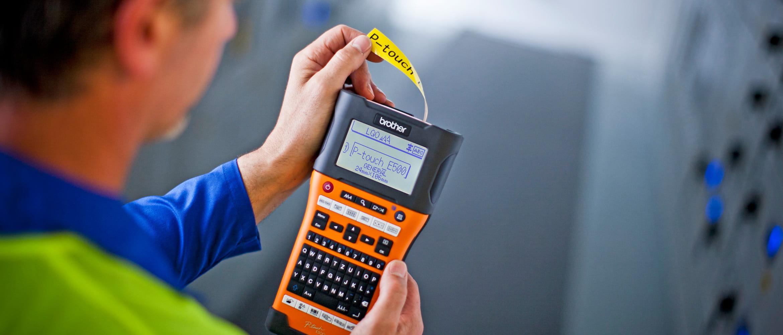 Technischer Mitarbeiter, P-touch E500 in der Hand haltend, Industrieanlage im Hintergrund