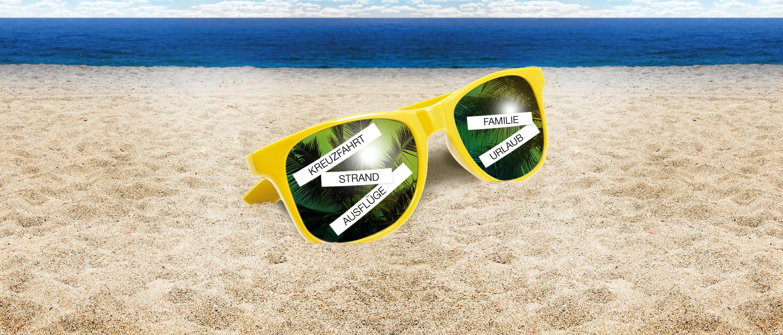 Gelbe Sonnenbrille mit P-touch Etiketten beklebt, im Sand liegen, Meer im Hintergrund