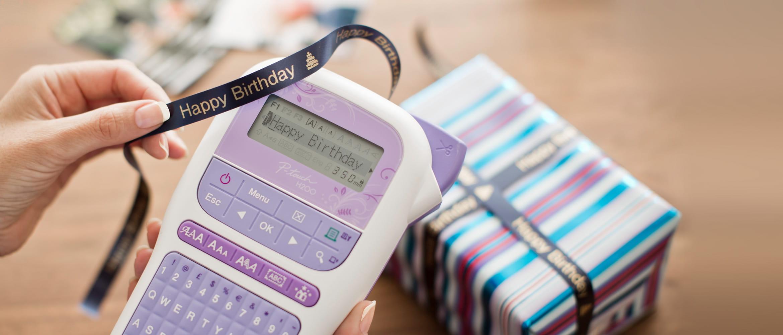 Brother P-touch H200 druckt gerade dunkelblaues Textilband mit Goldschrift, dekoriertes Geschenkpaket im Hintergrund