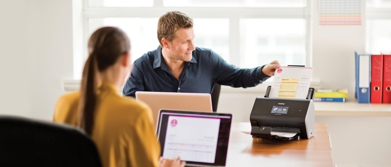 Mann und Frau an Schreibtisch sitzend, scannen Dokumente an Brother Scanner ein