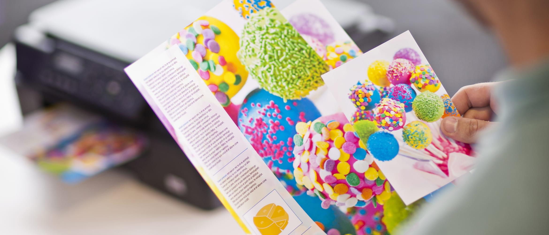 Person hält bunte Farbausdrucke in der Hand, Drucker im Hintergrund