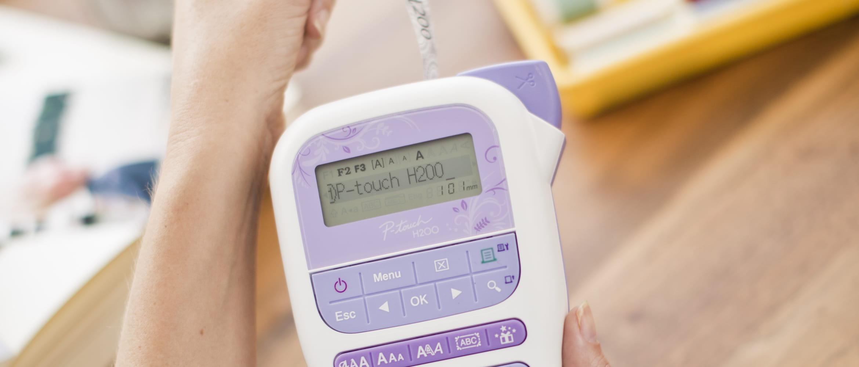 Brother PT-H200 druckt gerade Etikett aus, in der Hand gehalten