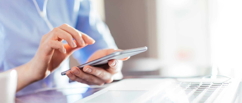 Frau sitzt vor Laptop und tippt auf ihrem Mobiltelefon