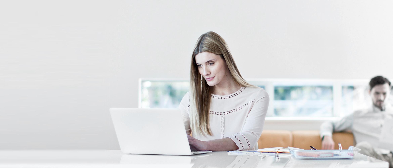 Frau in Büro an Laptop sitzend, Mann auf Couch im Büro im Hintergrund