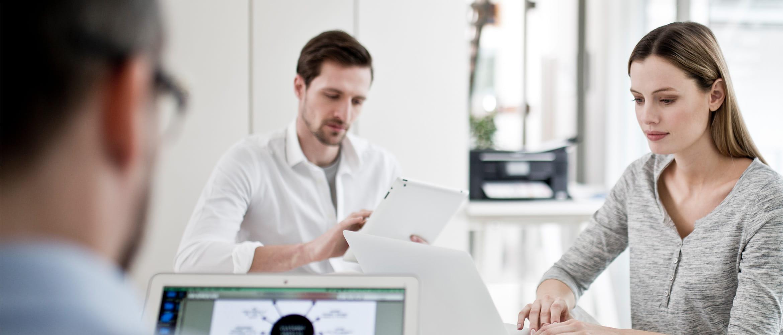Büromitarbeiter im Office, an Laptop sitzend, Brother Drucker im Hintergrund