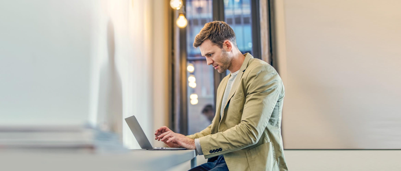 Mann stehend vor einem Laptop