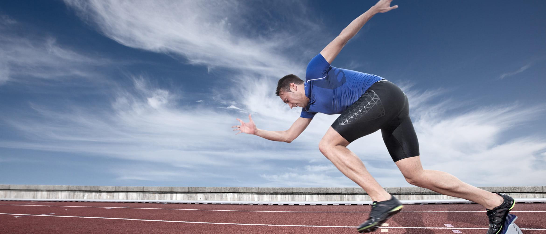 Sprinter in blauem Trikot, startet aus Startblock auf Tartanbahn