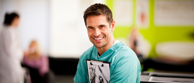 Lächelnder Arzt im grünen Kittel mit Klemmbrett in der Hand