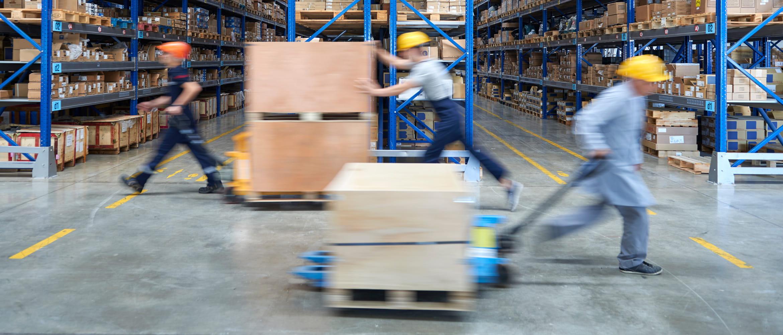 Mitarbeiter in der Logistik transportieren Pakete mit Hubwagen