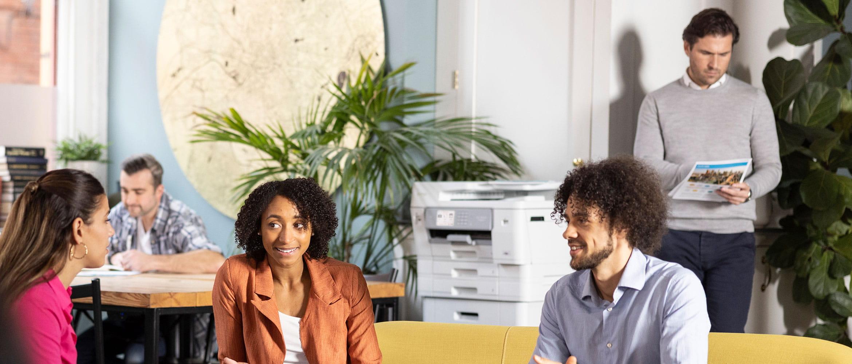 Mann und Frau im Gespräch, stehend, Brother Laserdrucker im Hintergrund