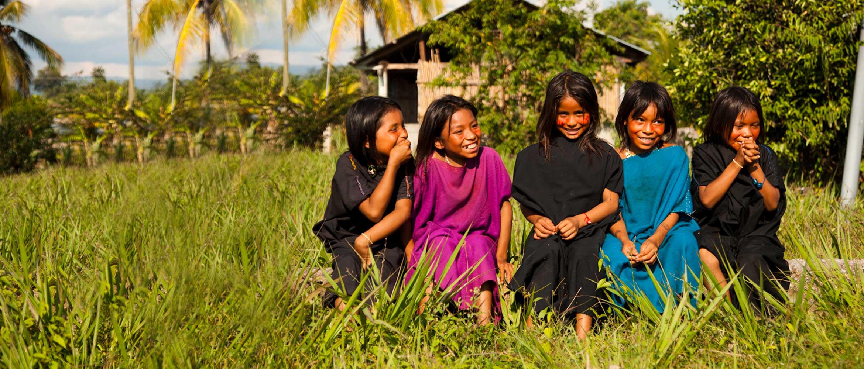 Kinder von Ureinwohnern, auf einer Wiese im Regenwald sitzend und lachend