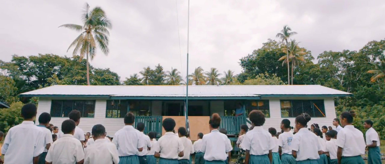 Gruppe von Schulkindern vor Schule im Regenwald