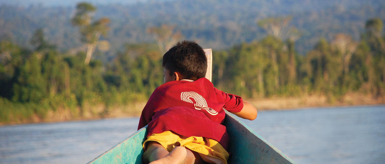 Junge auf einem Fischerboot liegend, welches auf einem Fluss im Regenwald schwimmt