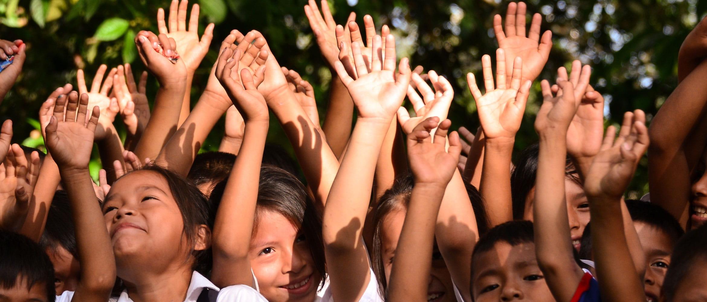Kindern lächelnd, heben winkend die Arme und Hände in die Luft
