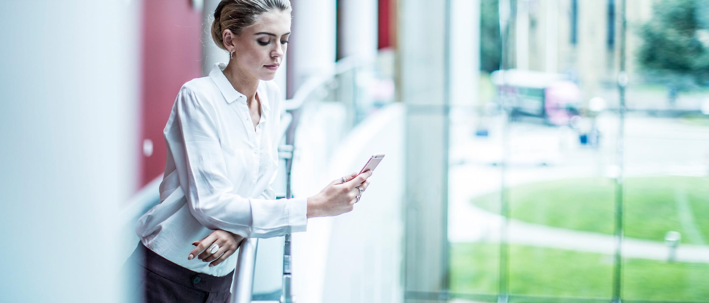 Frau lehnt an einem Geländer und schaut in ein Mobiltelefon