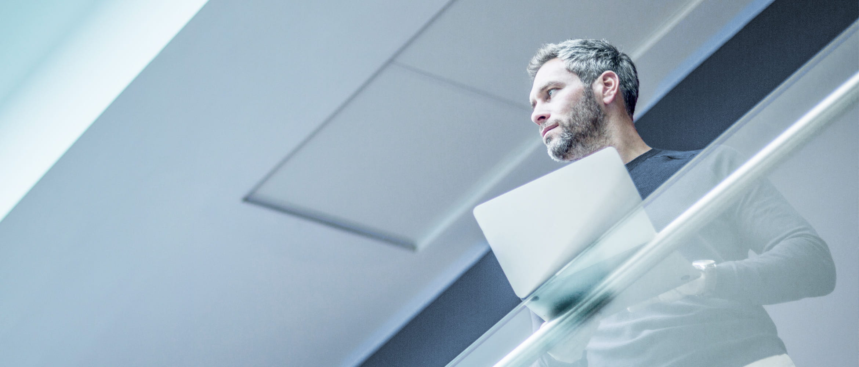 Mann mit Laptop leht an Glaswand