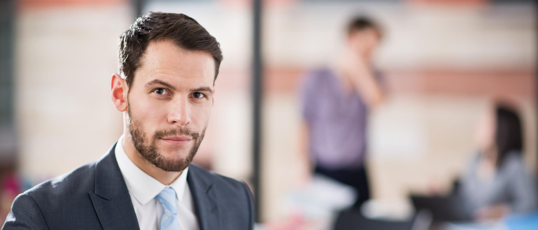 Mann im Anzug vor Kamera, Scanner und Mitarbeitergespräch im Hintergrund