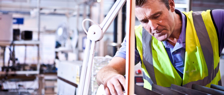Mitarbeiter in Produktionshalle während Montagearbeit
