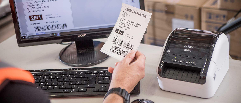 Brother QL-1100 desktop label printer on desk with person sat at desk holding label