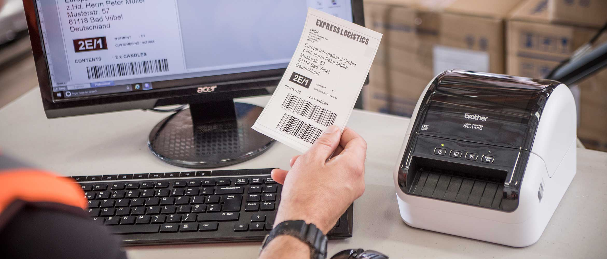 Brother QL-1100 desktop label printer on desk with person sat at desk holding label