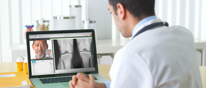 Arzt im Patientengespräch per Videokonferenz, vor Laptop sitzend