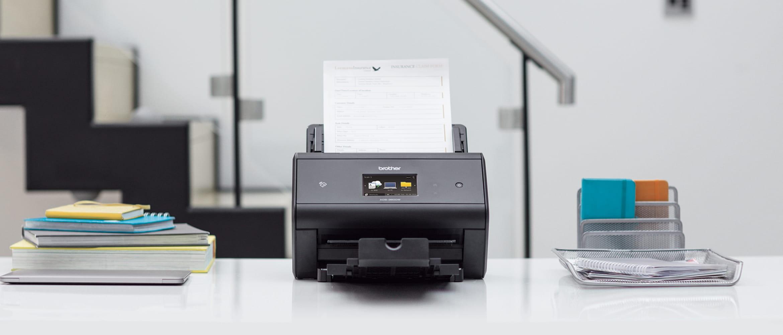 Brother ADS-3600W Scanner in Frontansicht auf Tisch stehend, Büro mit Treppe im Hintergrund
