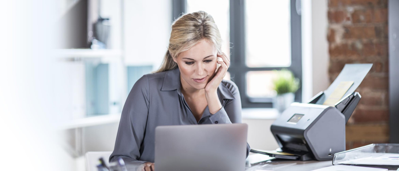 Frau am Schreibtisch sitzend, schaut in Laptop, Brother Scanner daneben