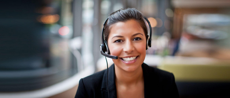 Lächelnde Frau mit Headset lächelt in Kamera