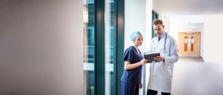 Arzt im weißen Kittel und Stethoskop mit Ärztin auf dem Flur des Krankenhauses