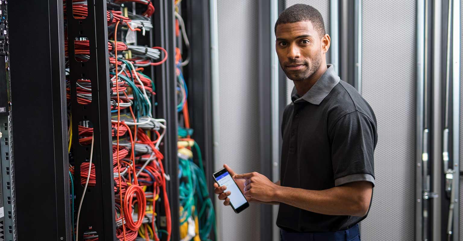 Netzwerktechniker, der die Brother iLink & Label App auf seinem Smartphone verwendet