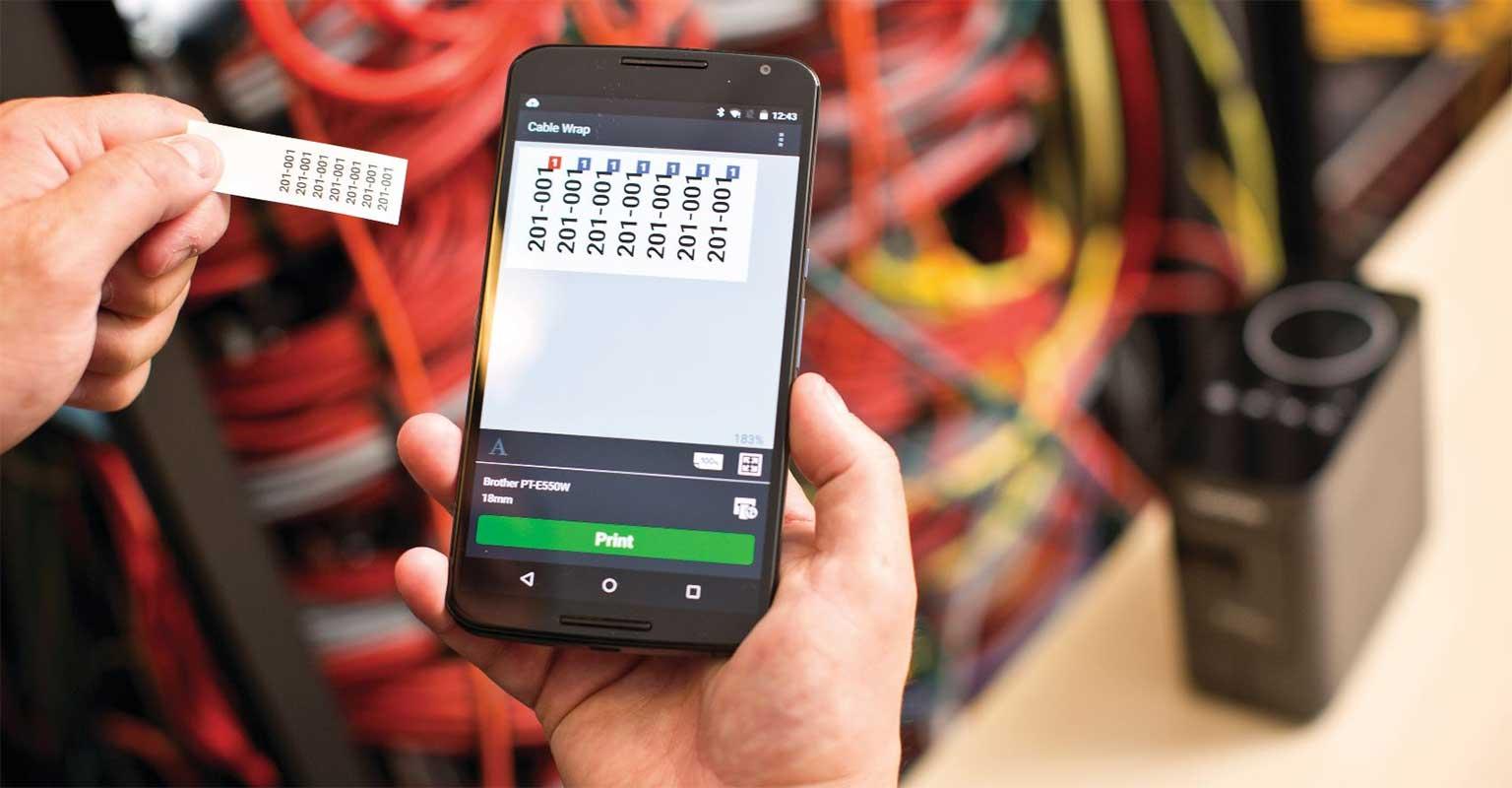 Etikettendruck auf einem Brother P-touch, der in der Hand gehalten wird, um den Etikettendruck vor Ort zu demonstrieren
