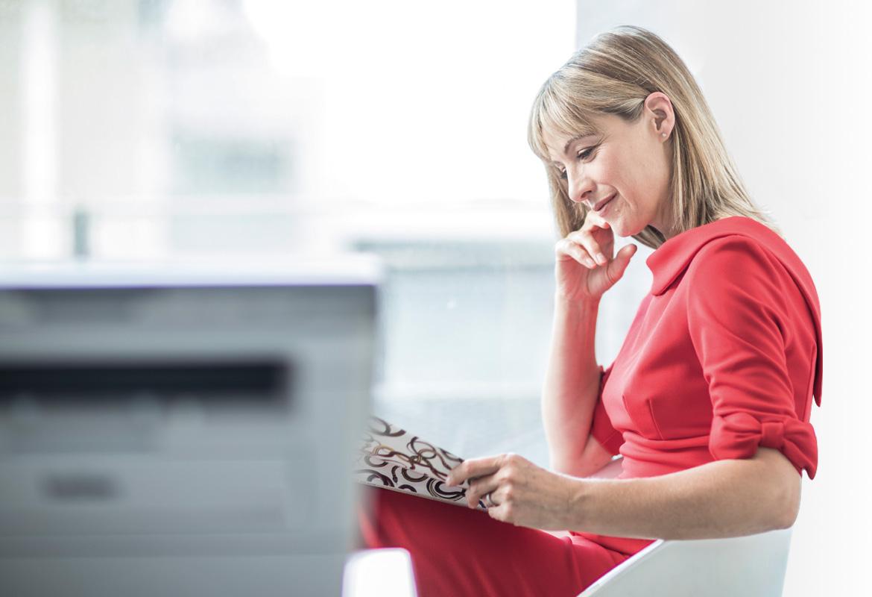 Frau liest Zeitung mit Drucker im Hintergrund
