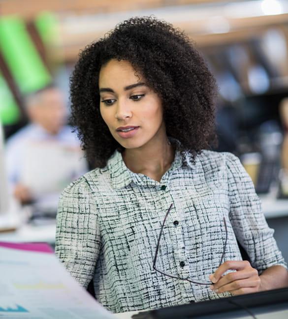 Kreativagentur Mitarbeiter am Schreibtisch, Fabrausdruck in der Hand haltend
