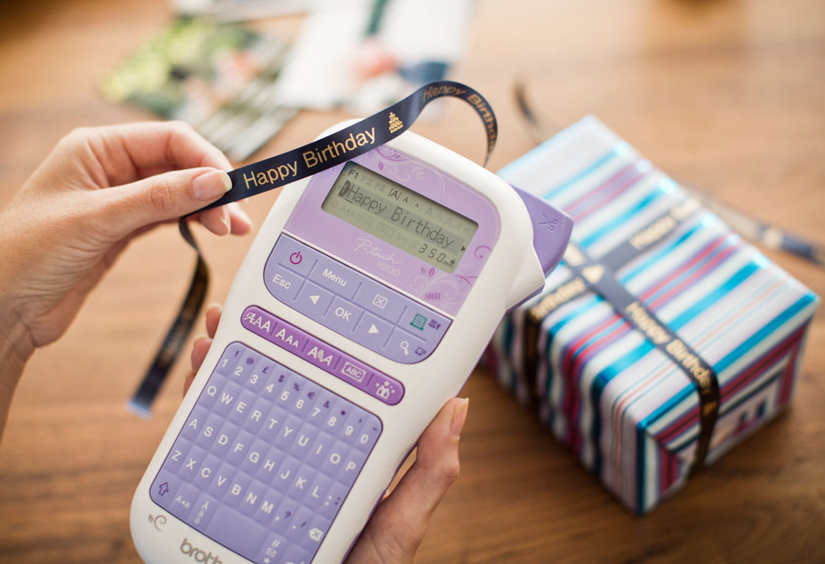 A Brother P-touch H200 label and ribbon printer is being used to create a happy birthday ribbon for gift wrapping