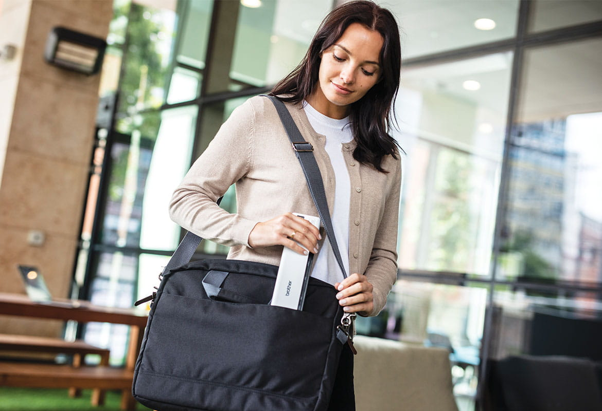 Female with brown hair wearing beige cardigan walking outdoors putting scanner in laptop bag, wooden table, glass window