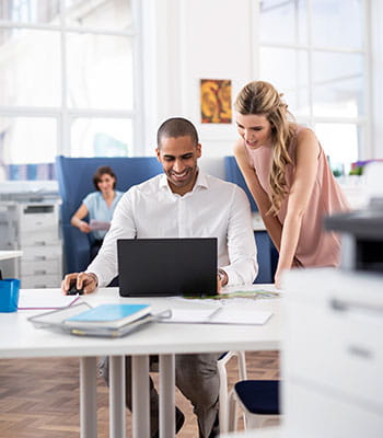 Woman wearing glasses stood with cup taking to woman sat on desk in a busy office, printers, man in suit, computers, paper