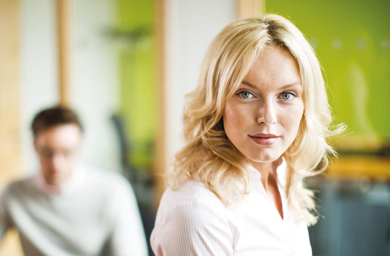 Büroumgebung, blonde Frau, fokussierter Blick, Mann an Schreibtisch im Hintergrund