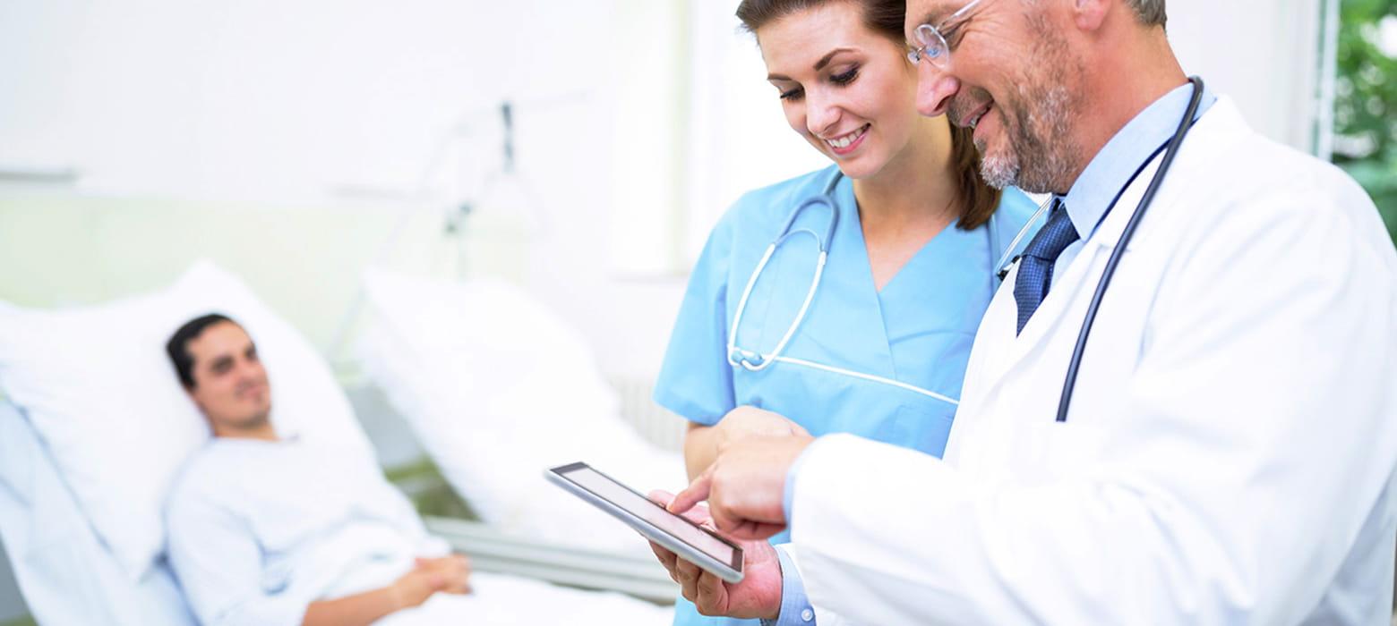 Arzt bespricht mit Krankenschwester über ein Tablet weitere Behandlung