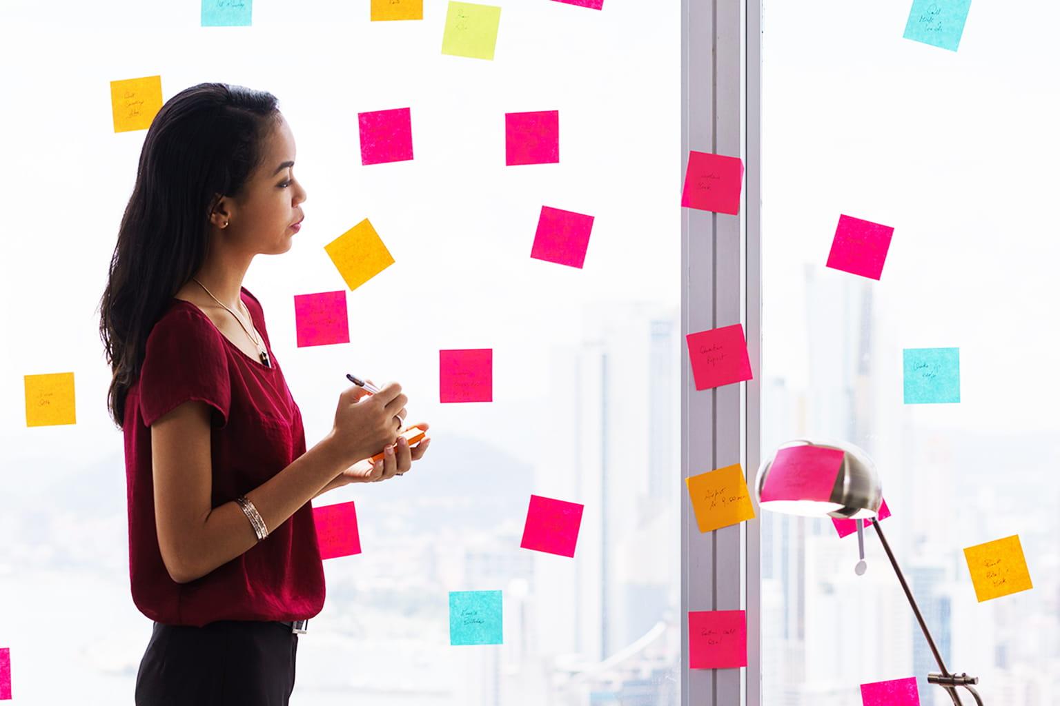 Frau klebt Post-Its mit Notizen an eine Fensterscheibe