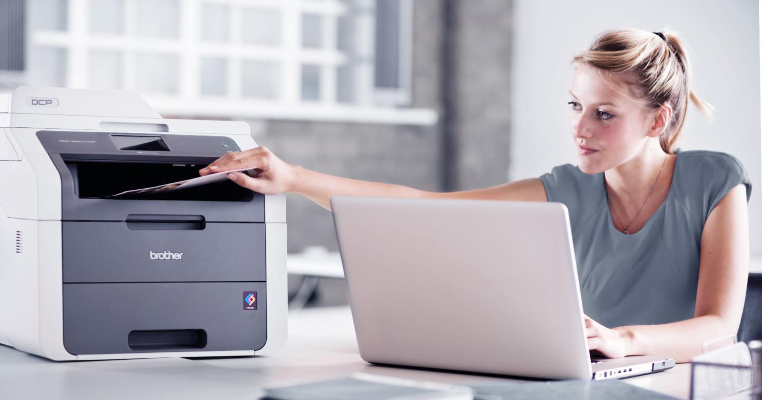 Frau druckt von ihrem Laptop Dokumente aus